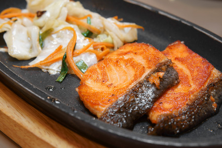 delicious Teppanyaki Salmon grill food with vegetable in the iron pan and wood chopping board on the table at Japanese restaurant for lunch or dinner