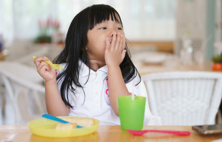 Asian children cute or kid girl enjoy eating dessert and bread delicious with colorful container or utensil plastic for baby on wood table and white chair in restaurant or cafe for breakfast and lunch