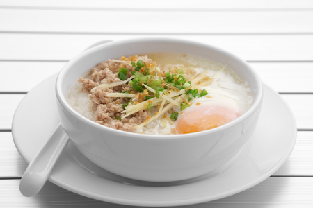 pork chops rice porridge or congee with soft boiled egg and vegetable in the white bowl with spoon on the aluminium table for delicious breakfast and clean food in the morning