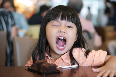 Asian children cute or kid girl enjoy and fun with happy eating delicious brownie chocolate cake for sweet dessert or snack on wood table and open mouth at lunch in restaurant or cafe for background