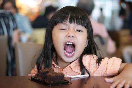 Asiatische Kinder süß oder Kind Mädchen genießen und Spaß mit glücklich essen köstlichen Brownie Schokoladenkuchen für süßes Dessert oder Snack auf Holztisch und offenen Mund beim Mittagessen im Restaurant oder Café für Hintergrund