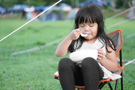 Asian children cute or kid girl and disheveled hair with hungry eating instant noodle delicious and sit on camping chair with green grass at nature camping tent trip on summer or rainy season holiday