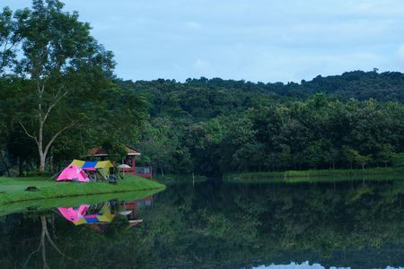 nature landscape pink camping tent and blue with yellow tarp on meadow with lake or river and tree mountain for holiday relax on rainy season and blue with gray sky and water reflection at ched khot Stock Photo