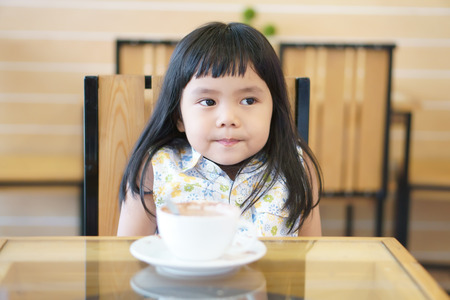 Asian children cute or kid girl smile and delicious hot cocoa or chocolate drink in white cup and funny or happy for breakfast in morning on table at home or cafe restaurant