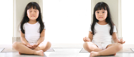 dual asian children cute or kid girl sit for meditation or yoga with open and close eye for peace or quiet and relax at temple or church and wear white dress with sunlight on white space background Reklamní fotografie