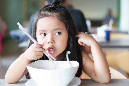 asian children cute or kid girl hungry and enjoy eating noodle delicious food in white bowl on wood table and use chopstick for breakfast or lunch at cafe restaurant or food court