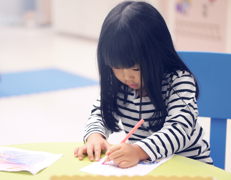 Asian children cute or kid girl concentrate learning for coloring or hand drawing paint on white paper and colorful table with chair at nursery or pre school on soft focus and vintage blue