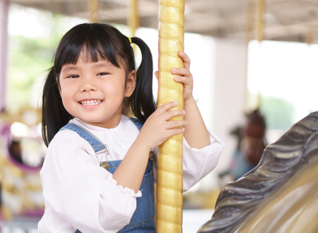 Asian children cute or kid girl enjoy smile and happy fun with riding horse or playing carousel in amusement park on summer holiday relax and family vacation