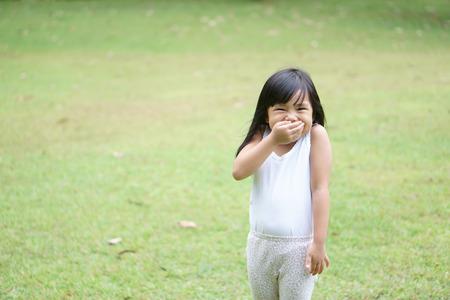 Les enfants asiatiques mignons ou kid girl stand sourire avec rire et main fermer la bouche pour un plaisir heureux avec profiter ou bâillonner et secrets sur l'espace de prairie d'herbe verte avec un gilet blanc d'usure