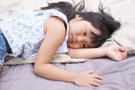 Asian children cute or kid fashion girl wake up in morning or sleeping and sad with unhappy or miss something on white bed lonely with brown pillow and bedtime in bedroom at home or hotel