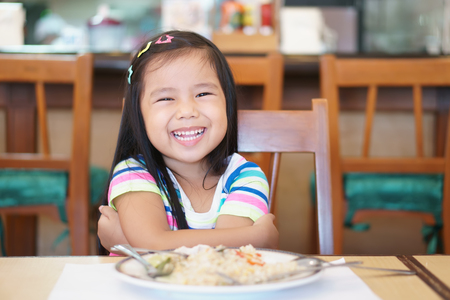 Asian children cute or kid girl enjoy eating fried rice delicious food on wood table with smile and laugh or happy for breakfast or lunch in restaurant or nursery school and kindergarten canteen