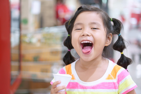 asian children cute or kid girl thirsty and drinking cold water in white paper cone cup for healthy and open mouth with tongue and make refreshing face in department store or super market
