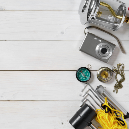 adventure travel equipment and camping for holiday lantern, camera, tripod, compass, vintage clock, rubber hammer, anchor and tent rope on white wood floor or table top view for background with space Stock Photo