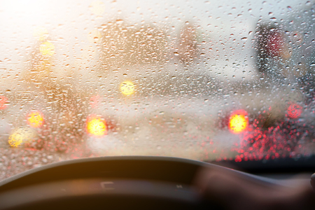 people driving car and water droplet on car mirror or windshield with rain storm and traffic jam on expressway road with red light at behind the car on warm sunlight