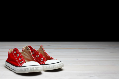 red canvas shoes or sneakers old for kids or baby and child foot on vintage white wood floor or table and black wall background on front view with copyspace isolated included clipping path