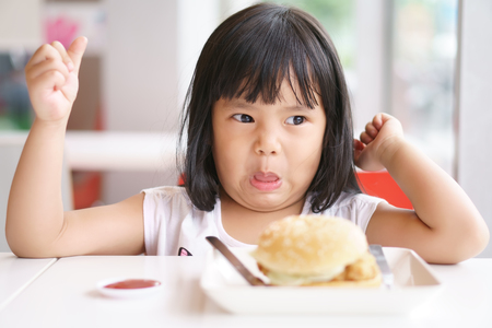 Asian children cute or kid girl eating ham burger or junk food with tomato sauce on white dish and table for breakfast or lunch and make face not delicious with unhappy or don't like at restaurant