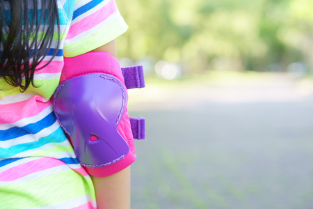 elbow protection support or pink greave for prevent injuries with safety on children arm and playing with riding scooter or bike and roller skate with sport exercise on public park and green garden 写真素材