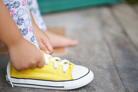 hand of children or kid girl learning and try tie yellow shoe laces or sneakers rope and footwear for walk travel and fashion on street with independent and free