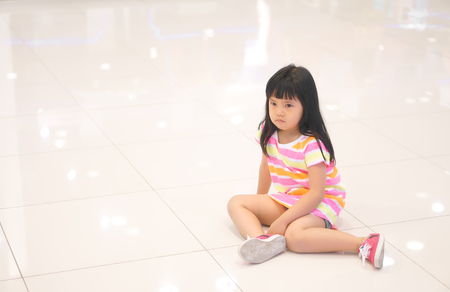 Asian children cute or kid girl sit upset or angry and sad feel with touchy on floor for buy toy in department store with space Standard-Bild