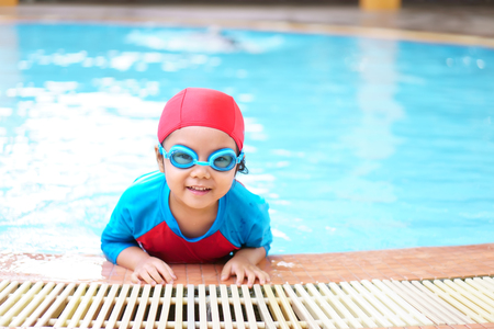 Asian children cute or kid girl wear swimming suit and goggles on swimming pool and smile with happy fun in water park for learning and training or refreshing and relax with exercise on summer holiday