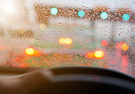 people driving car and water droplet on car mirror or windshield with rain or storm and traffic jam on expressway road although the green light with warm sunlight