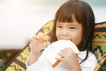 Asian children cute or kid girl fun and enjoy eating dessert and bread delicious for breakfast in morning with sunlight and sit on colorful chair on nature and picnic camping