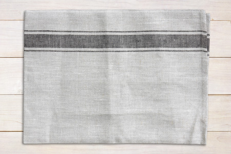 top view blank gray plate mat (napery) or dish towel and brown tablecloth on wood table in the kitchen and restaurant for your object and background or wallpaper Stockfoto