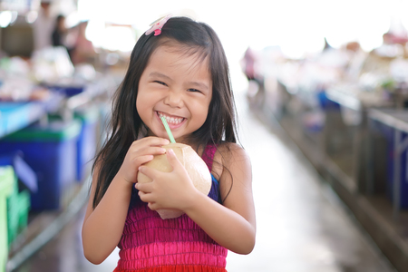 Asian children cute or kid girl smile and enjoy drinking perfume coconut juice or sweet fruit juice and cool by tube in the fresh market for refreshing and healthy on summer