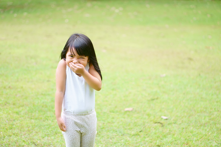 Asian children cute or kid girl cheerful stand smile with laugh and one hand close mouth for happy fun with enjoy or gag and secrets on green grass meadow space at school with wear white vest