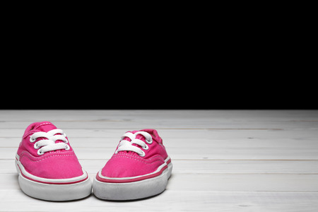 old secondhand pink canvas shoes or sneakers for kid or child and baby foot on vintage white wood floor or table and black wall front view for fashion with space and clipping path on black background