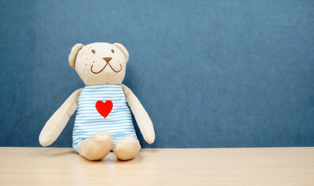brown teddy bear doll and smile with red heart on shirt sit on table or desk and blue wall background for gift on love valentine at kindergarten or nursery and home with space