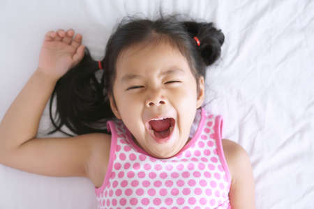 Asian child cute or kid girl sleep yawn and open mouth with stretch oneself after wake up late and sleepy in the morning on white bed in bedroom for relax on holiday with wear pink dress Banque d'images