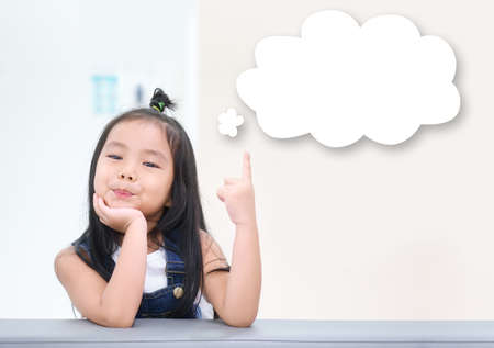 Asian child cute or kid girl thinking with finger pointing on top white cloud for new idea and happy fun or smile on sofa at preschool or nursery kindergarten and children hospital with brown space