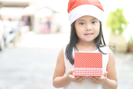 asian child or kid girl smile and wear red hat or santa claus suit and santie with holding empty red gift box for show and put gift for christmas or xmas and happy new year festival, focus on red box