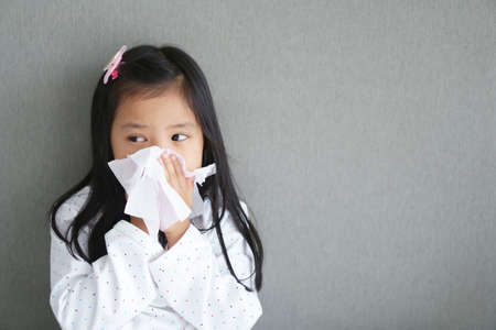 Asian child or kid girl sick and sad with sneezing on nose and cold cough on tissue paper because influenza and weak or virus and bacteria from dust weather and kindergarten school for medical BG Stockfoto