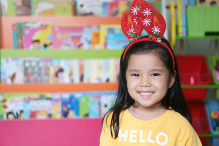 asian child or kid girl smile and wear red antler reindeer hair band or santa claus suit or santie for christmas or xmas and happy new year festival with fun on winter season and tale shelf background Stockfoto