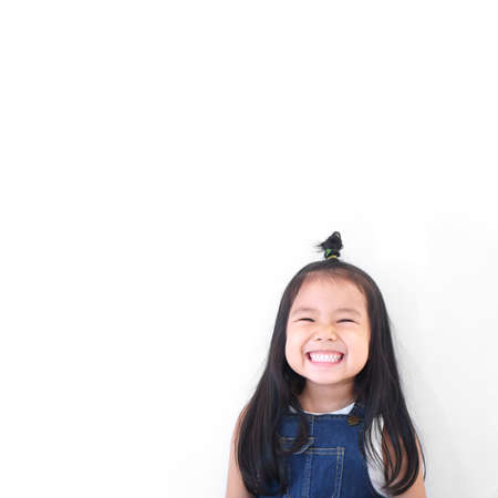 Asian children cute or kid girl and kindergarten student happy smile white teeth and laugh thinking for new idea with wear dungarees jean for fashion at school on white background with space isolated