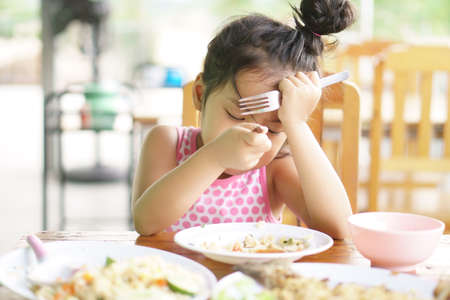 Asian child or kid girl anorexia or sad and bored food or boredom with not delicious and prop up or hand to head with headache on wood table for breakfast or lunch eating at restaurant on preschool