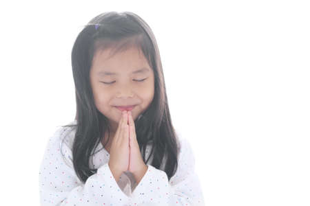Asian child smiling hand in hand or kid girl pay obeisance and pray close eye or hello welcome and thank you with wear white shirt in morning at church or temple for peace on white background isolated
