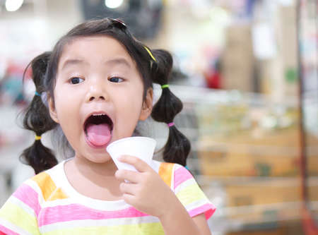 asian child or kid girl smile thirsty and drinking cold water in white paper cone cup for healthy and open mouth with tongue and make refreshing face in department store or super market and school Фото со стока
