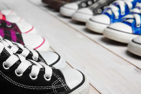 many canvas shoes or sneakers black, blue, pink, purple, brown and scott color old for kids or baby foot wear on vintage white wood floor or table for fashion and keep walking or background Banque d'images