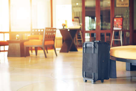 old black luggage or baggage travel in general airport reserved lounge or hotel reception and lobby for tourism travel concept or summer holiday vacation and check in on warm sunlight with space