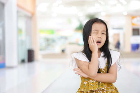 Asian child cute or kid girl toothache and caries or hypersensitive teeth with hand to cheek from eat sweet dessert or snack and do not brush teeth at children dental clinic or hospital with space Archivio Fotografico