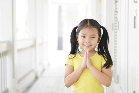 Asian child smiling hand in hand or kid girl pay obeisance and pray or hello welcome and thank you with wear yellow shirt in morning at church or temple for peace on white house receptionist at hotel