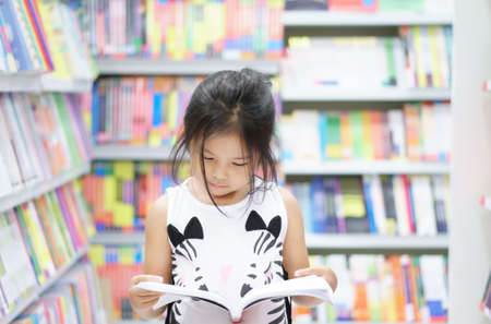 Asian child reading or kid girl happy smile and shopping or choose knowledge or text book on bookshelf in bookstore or library room at kindergarten school or nursery for learn and study with education Foto de archivo