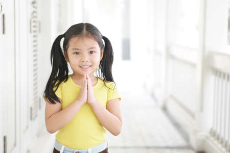 Asian child smiling hand in hand or kid girl pay obeisance and pray or hello welcome and thank you with wear yellow shirt in morning at church or temple for peace on white and receptionist at hotel