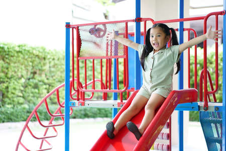 Asian child cute or kid girl smiling playing slider and happy fun or cheerful enjoy with extend arms on holiday relax exercise at playground public park in kids club or nursery kindergarten and school