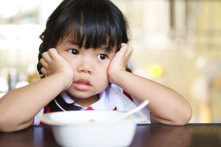 Asian child cute or kid girl student anorexia or bored with food and sad vacant with prop up or hand to cheek on food table for breakfast before going to kindergarten preschool for summer study