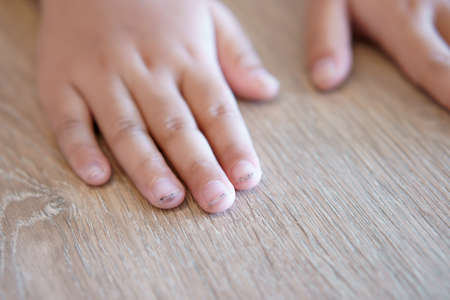 dirty and black nails and smelly with long nails on fingernail and child or kid hand with ugly and unclean to bacteria on wood table from play