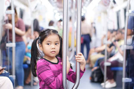 Asian child cute or kid girl smiling enjoy in bogey of sky train or electric train with underground railways or subway and holding rail for happy travel or transportation fun in city street on holiday